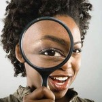 African American woman looking through magnifying glass