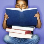 African American male child sitting with books.