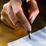 Woman Signing a Check